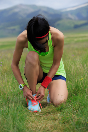 young fitness woman runner tying shoelace on grassland trail