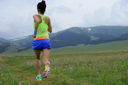 young sporty woman trail runner running on grassland Stock Photo