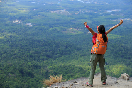 young asian woman hiker enjoy the view on mountain peak