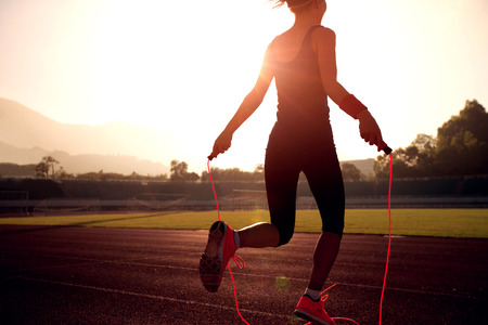 Young woman skipping rope during sunny morning on stadium track Stockfoto