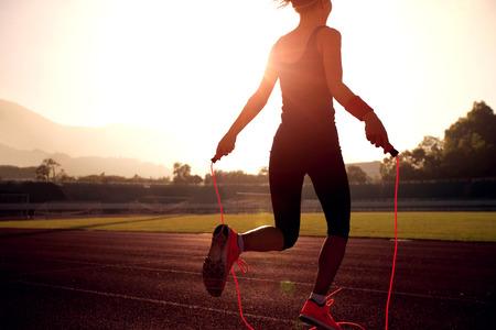 Mujer joven saltar la cuerda durante la mañana soleada en la pista del estadio Foto de archivo - 70052078