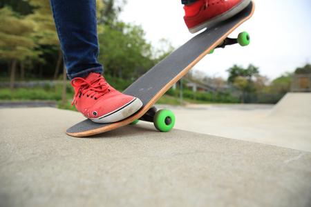 skate park: skateboarder legs riding skateboard at skatepark ramp