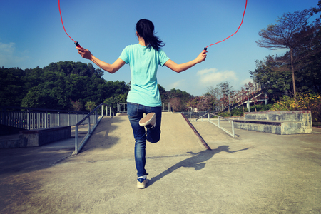 young fitness woman skipping rope outdoor