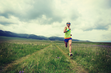 young fitness woman trail runner running on grassland Stock Photo