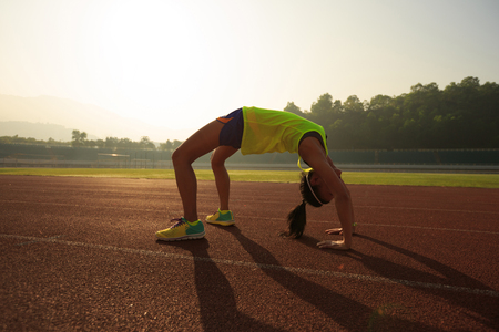 bend over: young asian woman backbending on stadium track