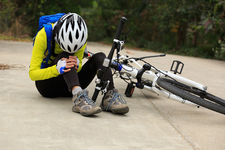 female cyclist getting injured while falling from mountain bike on forest trail Stock Photo