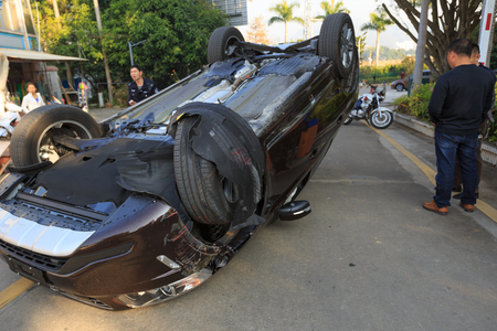 Car turned upside-down by accident on road Imagens