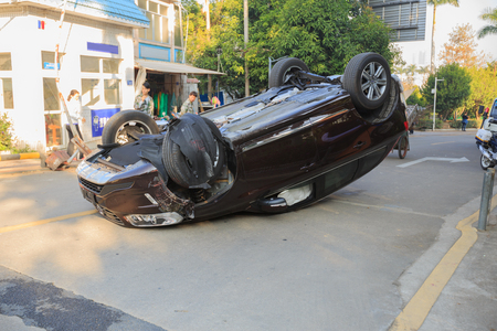 Car turned upside-down by accident on road Stockfoto