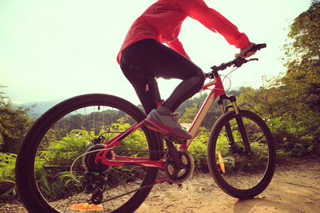 mtb: young woman cyclist riding mountain bike on forest trail