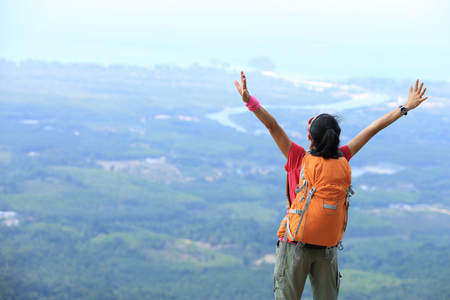cheering young woman hiker at  mountain peak Stock Photo