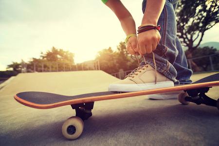 shoelace: young skateboarder tying shoelace on skateboard at skatepark ramp