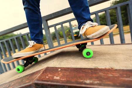 skate park: young skateboarder legs riding skateboard at skatepark