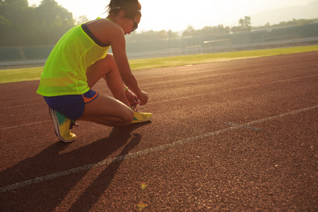 young fitness woman runner tying shoelace on stadium track