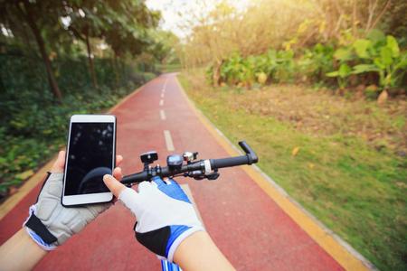 cyclist hands use gps navigator on smartphone while biking
