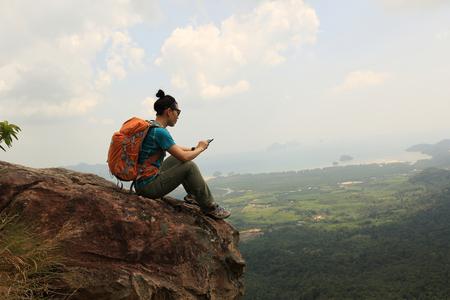 excursionista de mujer exitosa uso de teléfono móvil senderismo en el pico de la montaña