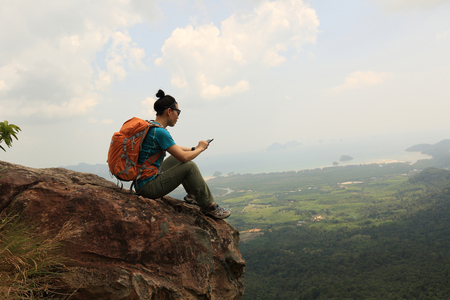photo edges: successful woman hiker use cellphone hiking on mountain peak