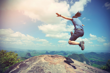 cheering successful young woman jumping on mountain peak
