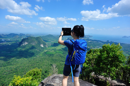 young woman backpacker taking photo with digital tablet on mountain peak