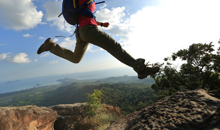 cheering successful young woman hiker jumping on mountain peak rock