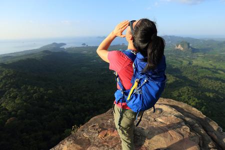 successful woman hiker shouting hiking on mountain peak