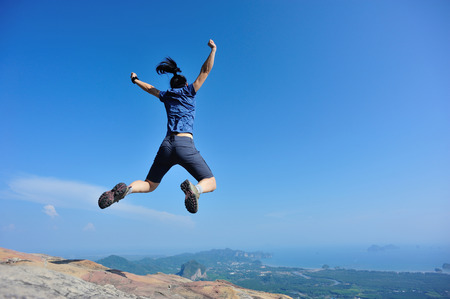 successful woman jumping on rocky mountain peak, freedom, risk, challenge, success concept
