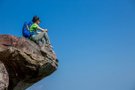 successful woman hiker taking photo with cellphone on mountain top Stock Photo