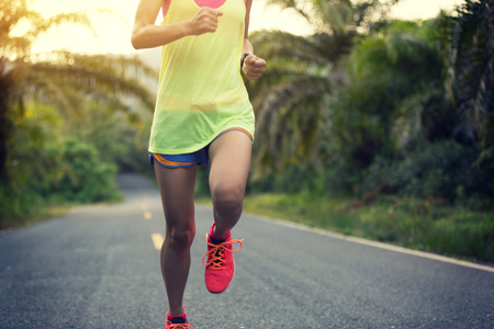 Young fitness woman running on tropical forest trail