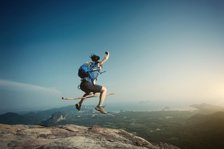 gritty: jumping on rocky mountain peak, freedom, risk, challenge, success concept Stock Photo