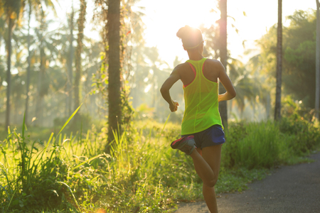 Young fitness woman running on morning tropical forest trail Stock Photo