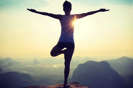 young fitness woman meditating on sunrise mountain peak Stock Photo