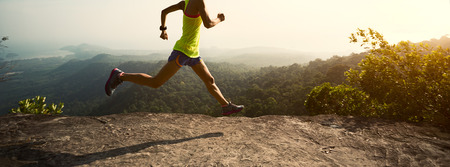 gritty: Young fitness woman trail runner running at mountain top