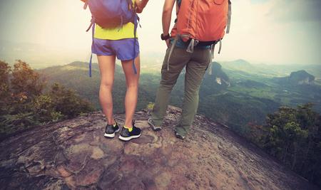 Twee backpackers wandelen op de bergtop genieten van het uitzicht Stockfoto