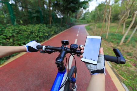 Ciclista utilizzare smartphone per la navigazione quando guida mountain bike sul sentiero della foresta Archivio Fotografico - 75906800