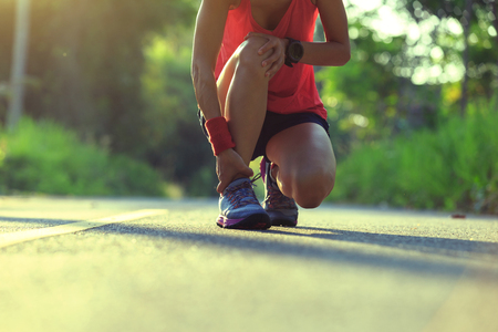 young fitness woman runner got sports injury on knee Stock Photo