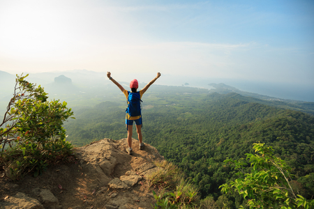 successful woman hiker open arms hiking on mountain peak