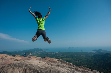 jumping on rocky mountain peak, freedom, risk, challenge, success concept Stock Photo