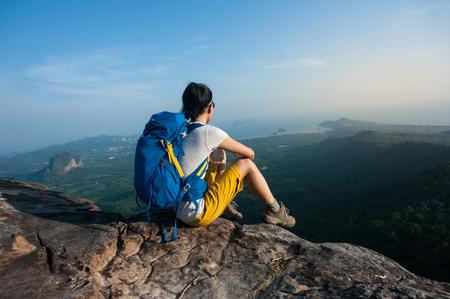 daredevil: successful woman hiker enjoy the view hiking on mountain peak