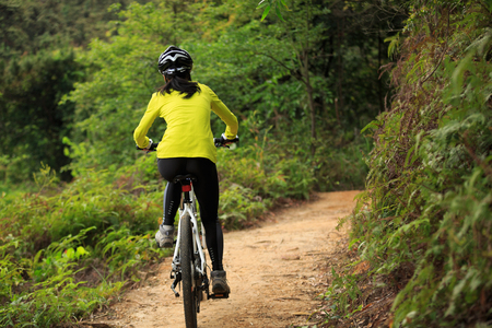 Young woman cyclist cycling mountain bike on forest trail