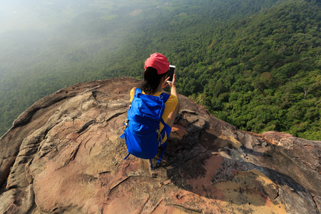 daredevil: successful woman hiker taking photo with smartphone on mountain peak cliff