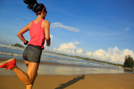 young fitness woman runner running on sunrise beach Stock Photo