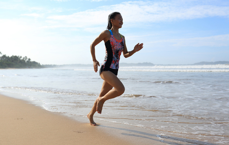 young fitness woman wear swimsuit running on beach Stock Photo