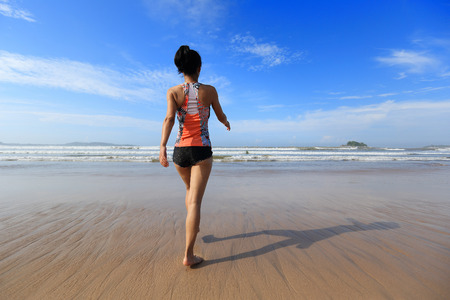 young fitness woman wear swimsuit walking to the sea