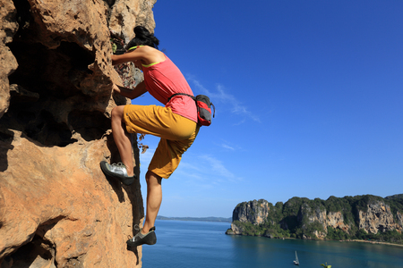 free solo woman rock climber climbing at seaside cliff