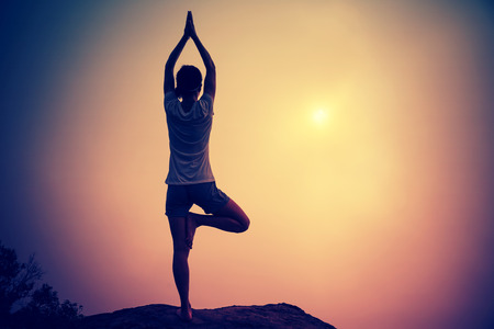 young fitness woman meditating on sunrise mountain peak Stock Photo