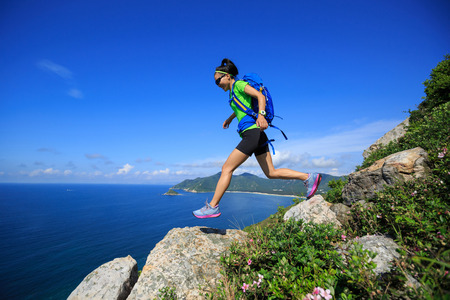 survive: successful hiker running on seaside mountain peak rock Stock Photo