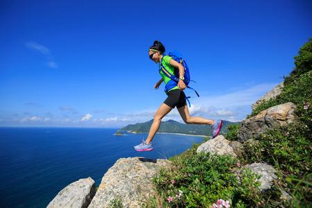 wanderlust: successful hiker running on seaside mountain peak rock Stock Photo