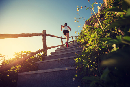 young fitness woman runner running upstairs on mountain stairs