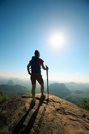 young woman hiker enjoy the view on sunrise mountain top rock