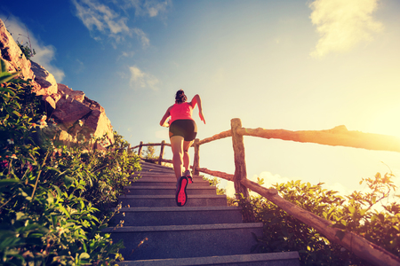 young fitness woman running upstairs on mountain stairs