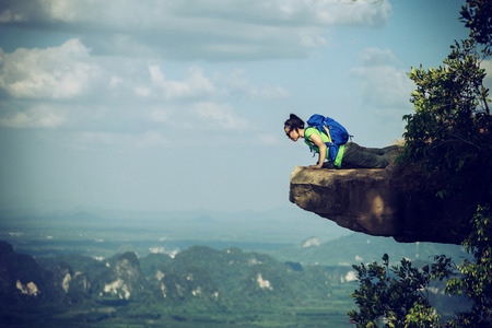 quirky: brave woman hiker lying on mountain cliff looking down